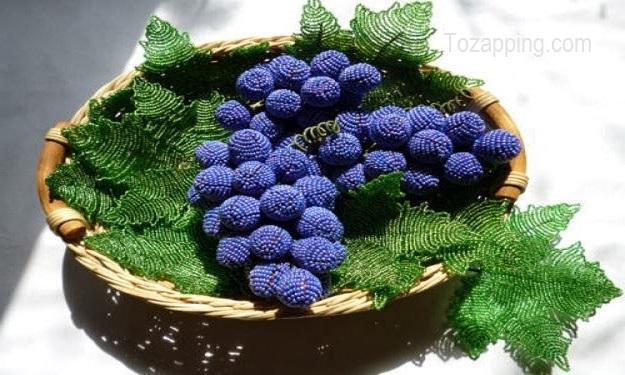 Parra con las uvas en un cesto Uvas hechas con cuentas